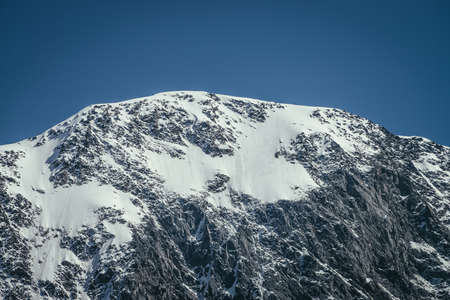 Awesome mountains landscape with black white snowy mountain top in sunny blue sky. Minimalist highland scenery with snow cornice on high mountain wall. Minimal view to wonderful snow-white pinnacle.