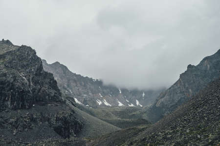 Dark atmospheric mountain landscape with gray low clouds in dark valley in high altitude in rainy weather. Big rocky mountain wall with snow in low clouds in gray cloudy sky. Gloomy mountain landscape