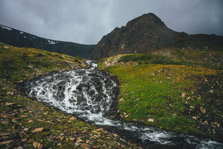 Atmospheric alpine landscape with beautiful mountain creek in green valley and great brown sharp pinnacle in overcast weather. Awesome highland view to mountain stream and sharp top under cloudy sky.