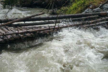 Fast turbulent river with broken bridge in water. Scenic mountain landscape with log bridge across river. Beautiful scenery with wooden bridge over mountain creek. Powerful rapids in mountain river. Standard-Bild