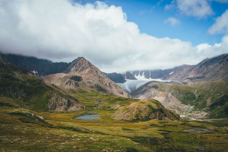 Scenic alpine landscape with mountain lake in sunlit green valley and glacier under cloudy sky. Awesome sunny scenery with beautiful glacial lake in sunlight against great mountain range in low clouds
