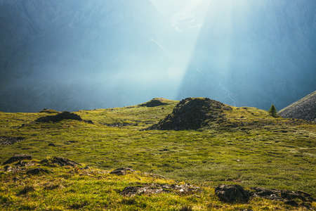Colorful green landscape with rocks and hills on background of giant mountain wall in sunlight. Minimalist vivid sunny scenery with sun beams and solar flare. Minimal alpine view. Scenic minimalism. Standard-Bild