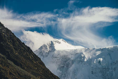Great view to high snowy mountain peaked top with low cloud under cirrus clouds in sky. Low clouds on big snow covered mountains with sharp pinnacle in sunshine. White-snow pointy peak in sunlight.
