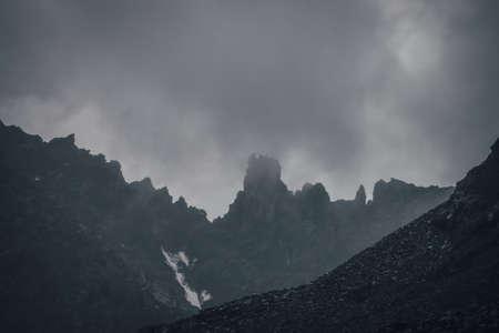 Dark atmospheric mountain landscape with black pointy rocky peak in gray cloudy sky. Lead gray low clouds among black mountains. Dark rocky pinnacle in low clouds in rainy weather. Gloomy minimalism. Standard-Bild