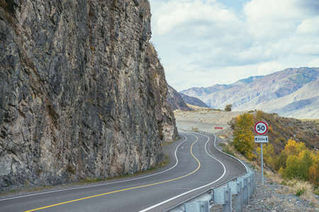 Colorful autumn landscape with mountain highway along rocks in sunshine. Bright alpine scenery with mountain road in autumn colors. Highway in mountains in fall time. Road along beautiful rocky wall. Standard-Bild