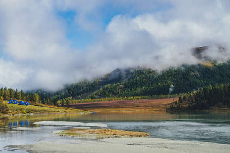 Scenic autumn landscape with reflection of gold sunlight in mountain lake and mountains in low clouds. Colorful sunny scenery with golden lake with view to sunlit forest hills in low cloud in autumn.