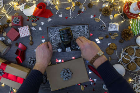 Young caucasian male packing a hipster camera as a present for Christmas, high angle overhead view Reklamní fotografie