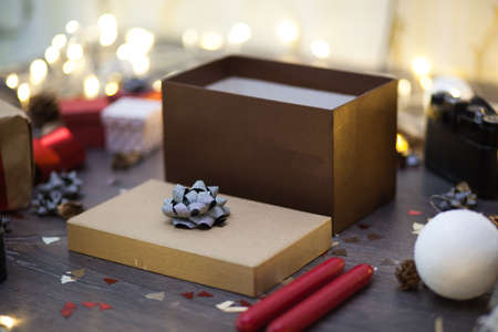 Brown gift box standing on a rustic wooden table with Christmas decorations Reklamní fotografie