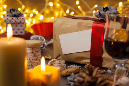 Brown gift box standing on a rustic wooden table with Christmas decorations, blank greeting card Reklamní fotografie