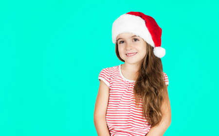 Little bright beautiful girl emotionally posing in Santa hat on an isolated turquoise background