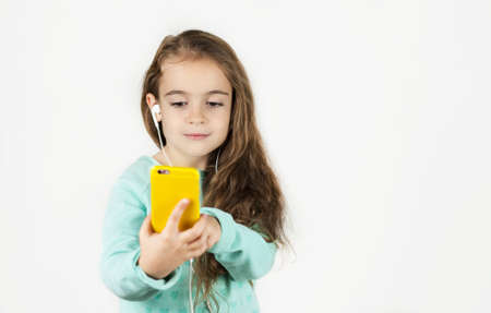 Bright beautiful little girl in headphones with a phone in her hands emotionally talks and rejoices on an isolated background.