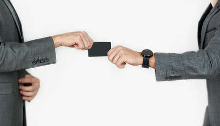 hands of men transferring a credit card or business card on an isolated background