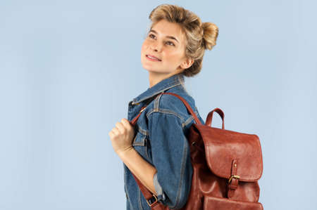 Happy beautiful student girl in a denim jacket with a backpack on her shoulders in the studio on a blue background. The concept of education and learning.