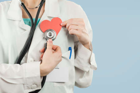 Young beautiful girl doctor with a red heart in her hands on a blue isolated background.Concept of love