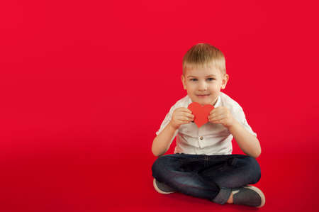 for holidays, lovers day and mothers day, baby boy sits on a red background with a red heart in his hands. The concept is to give gifts and love