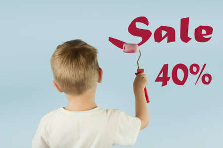 Beautiful blond child boy paints the wall with a roller and writes paint on the wall on an isolated blue background. Concept of discounts and sales
