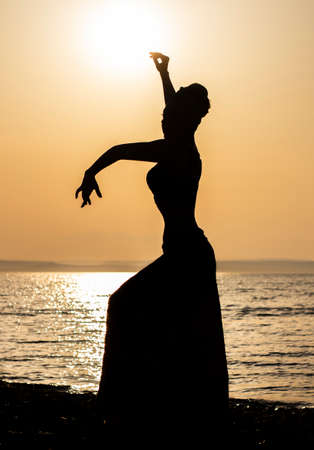 Silhouette dancing woman in sunset rays on a lake shore.