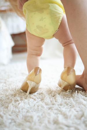 foto van klein babymeisje in hoge hakken schoenen