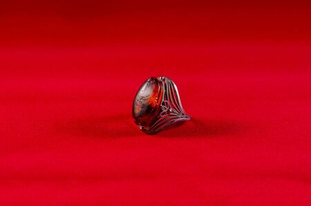 finery: Ring with amber on a red background. Stock Photo