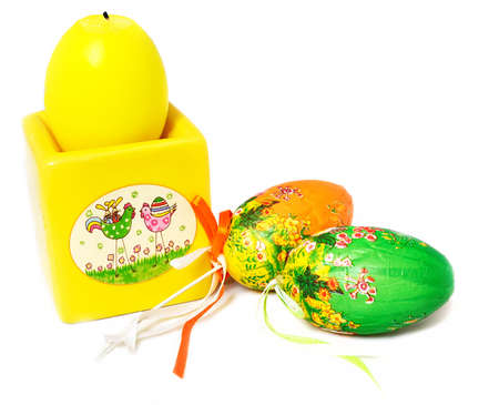 easter candle:  yellow easter candle and decorative eggs isolated on white