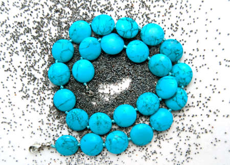 neckless: blue neckless over poppy seeds background