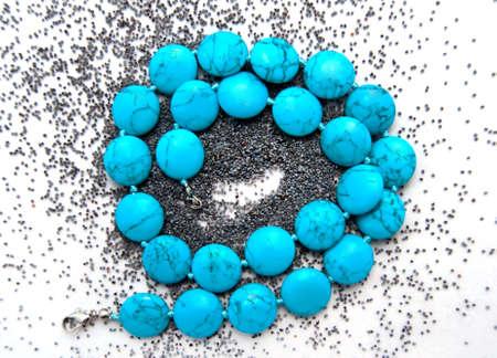 neckless: spring blue neckless over poppy seeds background