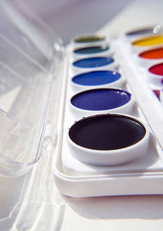 Colorful palette of watercolors .paints box on grey photo