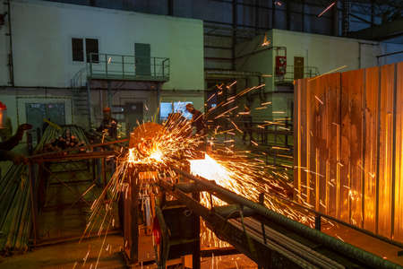 Disc machine for cutting metal. Cutting rebar with a large diameter abrasive disc. Hot metal particles as a result of the work of an angle grinder.