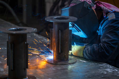 Welder working with electrode at semi automatic arc welding in manufacturing production plant.