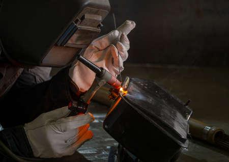 Welding the fuel tank of a motor pump by electric arc welding in argon shielding gas.
