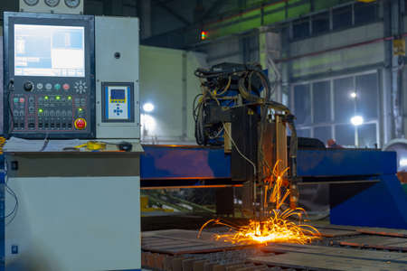 Operator controls numerically controlled machine. Gas cutting of sheet steel on a machine with numerical control.
