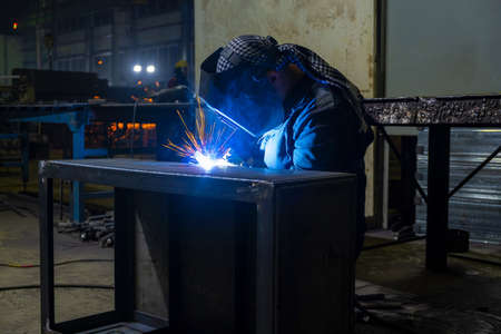 The welder performs metal construction welding with semi-automatic electric arc welding.