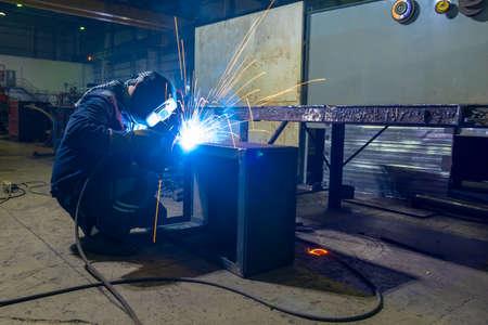 Welder performs welding work semi-automatic electric arc welding.