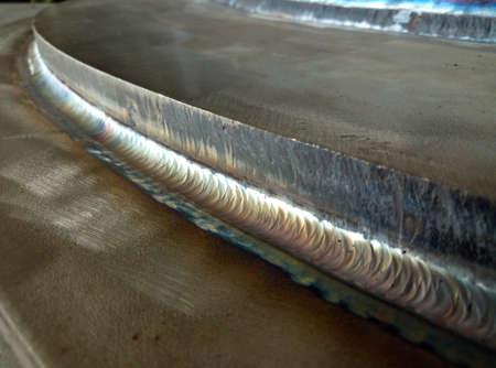 Welding the fuel tank of a motor pump by electric arc welding in argon shielding gas. TIG welding.