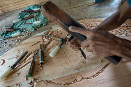Hands of a master carve a pattern on a wooden blank using hand tools. Wood carving.