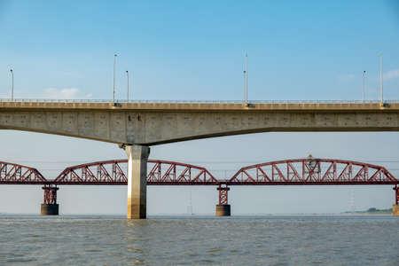Reinforced concrete bridge over the river. Big beautiful automobile bridge. Fast river.