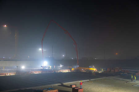 Pouring the foundation with a concrete pump. Night shift work. Continuous production.