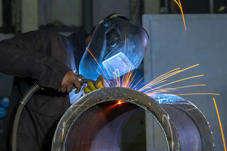 Welder performs welding work semi-automatic electric arc welding. Pipe production. MIG welding.