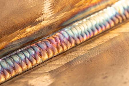 Welding of stainless steel with argon arc welding. Welding TIG. Color welding seam.
