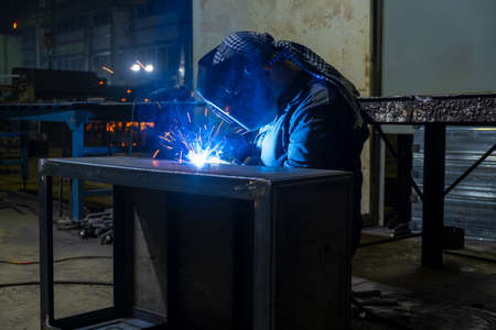 Welder performs welding work semi-automatic electric arc welding. Assembly of metal structures. MIG welding. Imagens