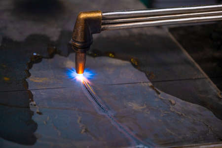 The worker performs the cutting of sheet steel with a gas cutter. Gas cutter. Stok Fotoğraf