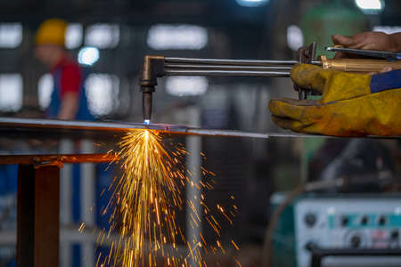 The worker performs the cutting of sheet steel with a gas cutter. Gas cutter.