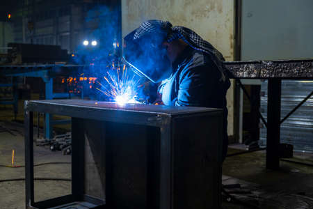 Welder performs welding work semi-automatic electric arc welding. Assembly of metal structures. MIG welding.