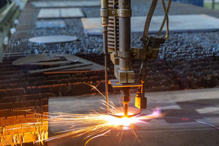 Gas cutting of sheet steel on a machine with numerical control. Splashes of molten metal.