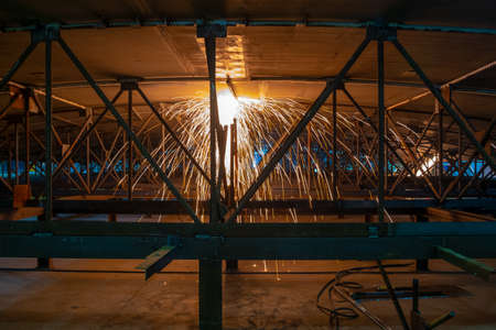 Assembly of metal structures. Working with metal using an angle grinder. Hot metal particles resulting from the operation of an angle grinder. Banco de Imagens