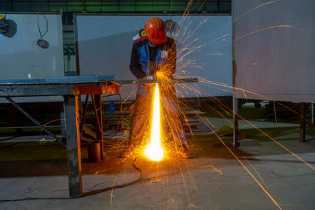Procurement of parts for the further production of metal structures. Cutting a steel corner with an angle grinder. Banco de Imagens