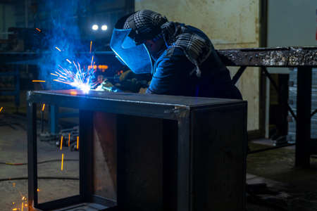 Welder performs welding work semi-automatic electric arc welding. Assembly of metal structures. Imagens