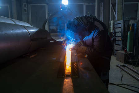 Worker performs welding of metal structures. Semi-automatic manual welding. MIG welding.
