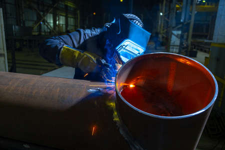 Welder working with electrode at semi automatic arc welding in manufacturing production plant. Welding method MIG.