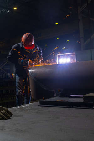 Manufacturing of steel pipes in one of the plant's workshops. Rotation of the angle grinder disc during operation. Bright sparks from metal cutting. Preparation of metal structures before welding.